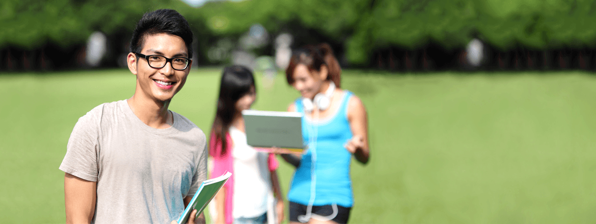 Student holding NCEA books on field